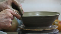 Craftsman making plate on pottery wheel - stock footage