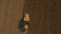 Aerial of yellow combine harvester driving through and harvesting corn field Stock Footage
