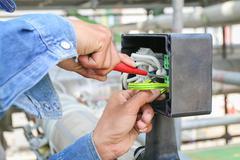 technician use screwdriver tighten nut - stock photo