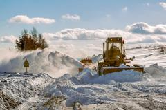 Grader cleaning road in winter Stock Photos