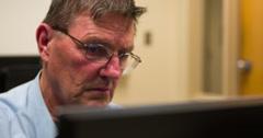 Elderly man working at computer 4k Stock Footage