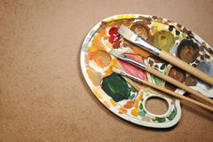 Dirty palette with paintbrushes on the cardboard paper, art background Stock Photos
