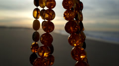 amber necklaces on the beach - stock footage