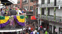 People throwing beads from balcony to Bourbon Street Stock Footage