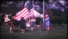 6 - girl scouts lower and fold flag then march away - vintage film home movie Stock Footage