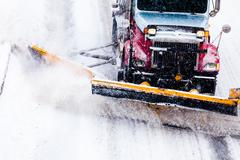 snowplow removing the snow from the highway during a snowstorm - stock photo