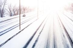 Disturbing sunset light and snowstorm on highway Stock Photos