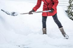 close-up of woman shoveling her parking lot - stock photo