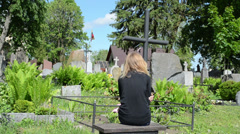 Widow woman near soldier father grave. Lithuania national flag Stock Footage