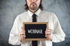 Webinar concept. businessman holding blackboard with webinar title Stock Photos