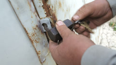 Closeup of man opening barn lock with keys Stock Footage
