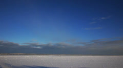 Frozen lake and small figures of man and dog under blue sky Stock Footage