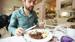 Handsome young man eating in a restaurant Stock Footage