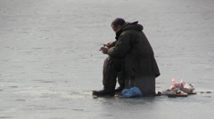 Fisherman Puts fishing rod to catch fish from the ice-hole on a frozen lake Stock Footage