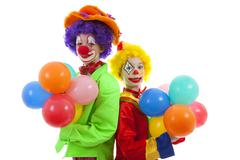 Children dressed as colorful funny clowns with balloons Stock Photos