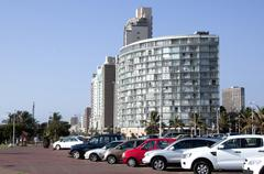 Car lined street outside hotels on durban beachfront Stock Photos