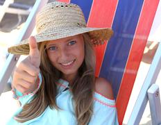 beautiful girl in hat show ok on beach - stock photo