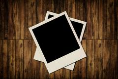 blank instant photo frames on old wooden background - stock illustration