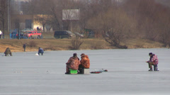 Fisherman catch fish with fishing rod from the ice-hole on a frozen lake surface Stock Footage