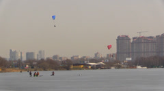 Paraglide Flies Among Frozen Lake, City, Fishermen Stock Footage