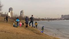 People enjoy the arrival of spring on the shore of a frozen lake Stock Footage