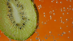 Kiwi in aerated water on orange background Stock Footage