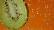 Stock Video Footage of kiwi in aerated water on orange background