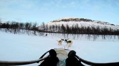 POV handler husky dogs as they pull sledge over snow covered terrain Norway Stock Footage