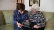 Stock Video Footage of Grandmother and grandson looking at family photo album, laughing, generations
