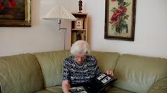 Nostalgic old woman looking at family photo album, memories, elderly female Stock Footage