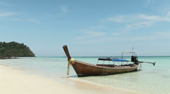 Long-tailed Boat on a beach with blue sky Stock Footage
