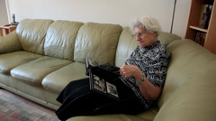 Nostalgic old woman looking at family photo album, memories, elderly female - stock footage