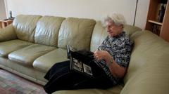 Nostalgic old woman looking at family photo album, memories, elderly female - stock footage