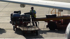 Baggage Handler offloading luggage, from an aircraft Stock Footage