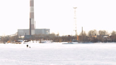 Snowmobile rides on the background of factory chimneys and smoke Stock Footage