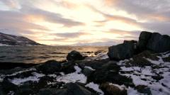 Norwegian Fjord waves on the shoreline winter snow fading sunlight nr Tromso - stock footage