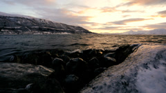 Norwegian Fjord waves shoreline winter snow fading sunlight nr Tromso - stock footage