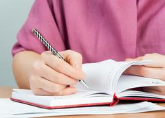 Woman writing in organizer Stock Photos
