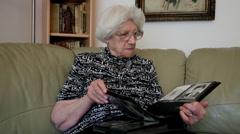 Nostalgic old woman looking at family photo album, memories, elderly female Stock Footage