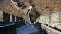 Great wall with snow and sunshine with hill in the background with chinese Stock Footage