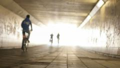Three Cyclists Cycling into the Light at the End of the Tunnel - 29,97FPS NTSC Stock Footage