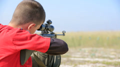 Young boy with air rifle shooting Stock Footage