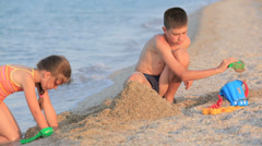 Boy and girl playing in a sand on the beach Stock Footage