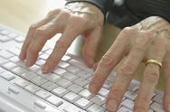 Stock Photo of senior hands on keyboard