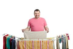 Stock Photo of smiling fat man in red t-shirt drying washing