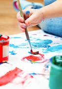 Closeup of baby hand holding paintbrush. Stock Photos
