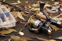 fishing tackle on wooden surface. - stock photo