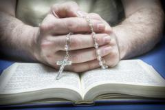 Christian believer praying to god with rosary in hand Stock Photos