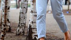 People walking past silver birch trees Stock Footage