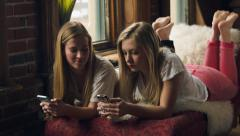 Two Pretty Teenage Girls Relax And Play On Their Phones - stock footage